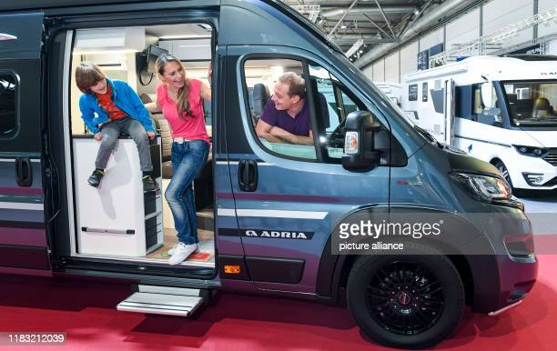 The model family Evelyn Weber Jupp Auferkamp and the sevenyearold Marc give a foretaste of the Touristik Caravaning fair at a camping bus from Adria...