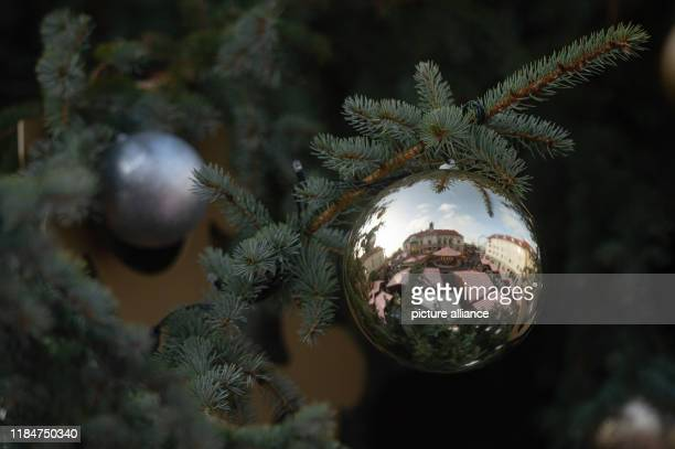 26 November 2019 SaxonyAnhalt Magdeburg The stalls of the Christmas market the town hall and the blue sky are reflected in a Christmas tree ball It...
