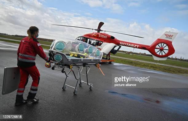 November 2020, Baden-Wuerttemberg, Rheinmünster: Gerhild Gruner, emergency physician, pushes an EpiShuttle in front of the intensive care helicopter...