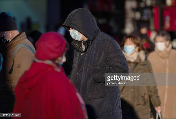 November 2020, Baden-Wuerttemberg, Stuttgart: Passers-by with mouth and nose masks are partly illuminated by the sun. In Baden-Württemberg, corona...