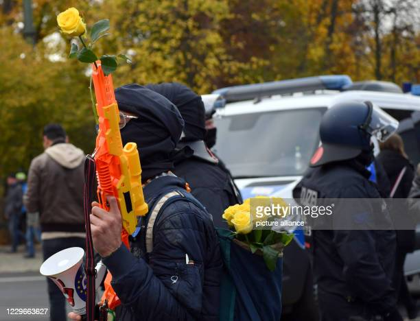 A participant in a demonstration against the Corona restrictions of the German government is carrying a plastic rifle with a yellow rose in front of...