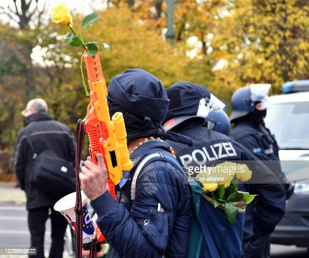 A participant of a demonstration against the corona restrictions of the German government carries a plastic rifle with a yellow rose in front of the...