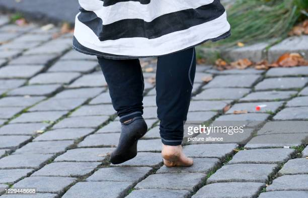 November 2020, Berlin: A woman walks across the pavement without shoes to take part in the meal that singer Frank Zander serves to homeless people at...