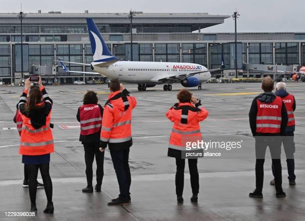 November 2020, Brandenburg, Schönefeld: Journalists watch a Boeing 737-800 of AnadoluJet, from the airline Turkish Airlines, taxiing after landing...