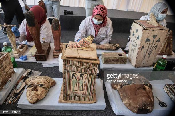 Egyptian archaeologists restore the newly discovered ancient statues during a press conference at Saqqara Egyptian antiquities officials announced...