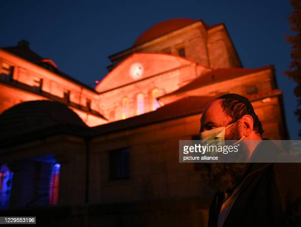 November 2020, Hessen, Frankfurt/Main: A man wearing a kippah and a mouth and nose protector stands in front of the illuminated Westend Synagogue....