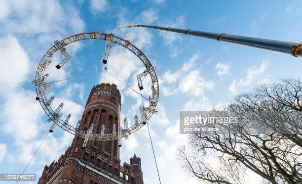 November 2020, Lower Saxony, Lüneburg: A crane lifts the so-called Wichernkranz onto the 56-meter-high water tower of the city. The Wichernkranz is...