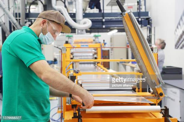 Florian Sorge is working on a machine that covers plastic with aluminium foil at the opening of a new technical centre at the Thuringian Institute...