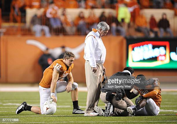 University of Texas Longhorns QB Colt McCoy and University of Texas Longhorns Head Coach Mack Brown watch as team trainers look at University of...