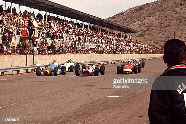 November 22, 1964: Drivers slow for a caution flag during the running of the Bobby Ball Memorial USAC Indy Car race at Phoenix International Raceway.