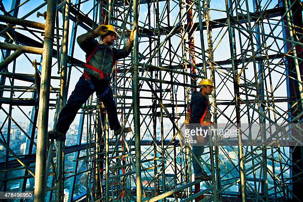 November 23 Flame Towers Baku Azerbaijan Construction workers inside the scaffolding of one of the three Flame Towers Inspired by Azerbaijans history...