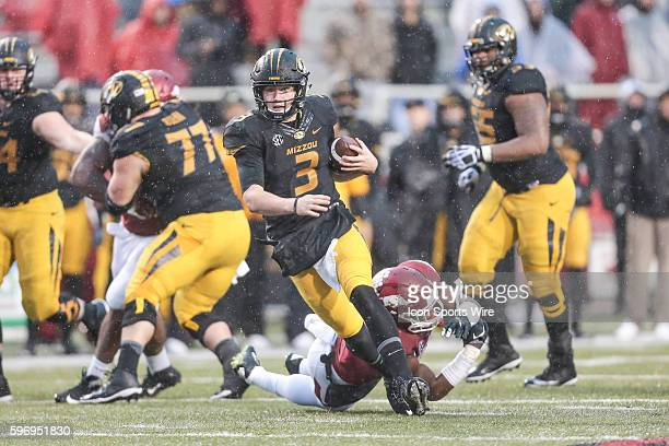 Missouri Tigers quarterback Drew Lock escapes the tackle of Arkansas Razorbacks linebacker Dre Greenlaw during an NCAA football game between the...