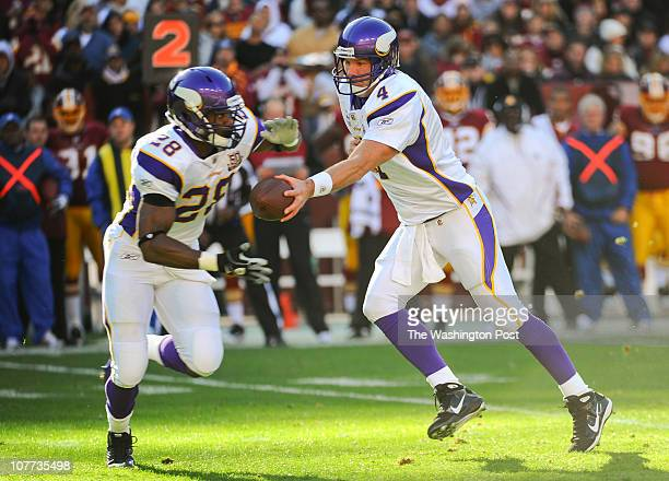 Brett Favre of the Minnesota Vikings hands off to Adrian Peterson during the first quarter against the Washington Redskins at FedEx Field in Landover...