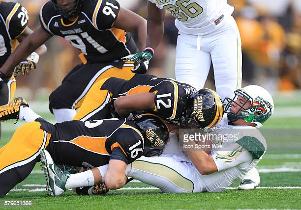 Southern Miss Golden Eagles defensive back Emmanuel Johnson and linebacker Elijah Parker take down UAB Blazers quarterback Cody Clements for a sack...