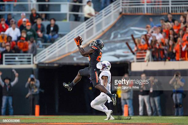 Oklahoma State Cowboys wide receiver James Washington leaps for a reception that he would run in for a touchdown during the Big 12 NCAA football game...