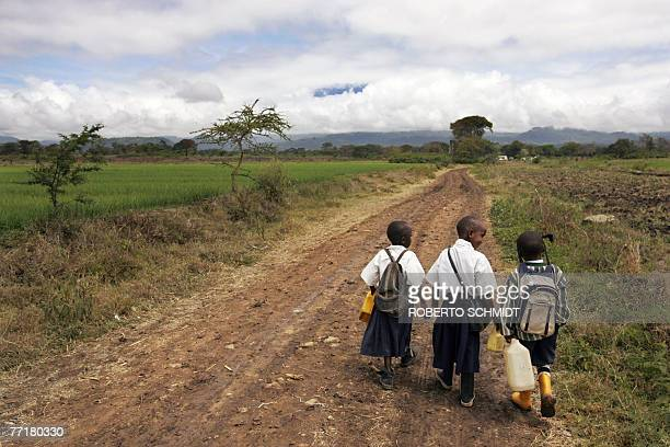 Novesa holds the hand of her fiveyearold neighbor Delvin as they and her younger brother Dixon walk down a country road to their school in the Usa...
