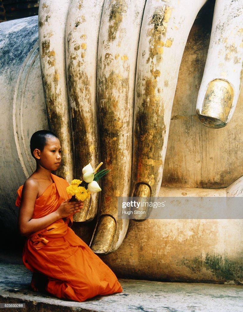 Novice Buddhist Monk Kneeling Next to Fingers of Statue : Stock Photo