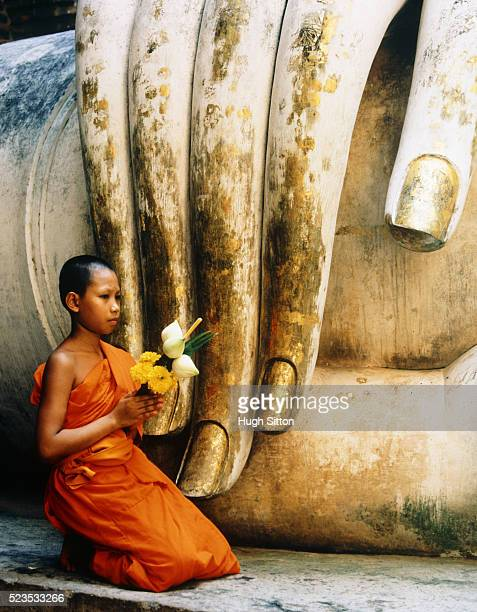 Novice Buddhist Monk Kneeling Next to Fingers of Statue