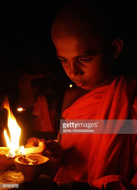 A novice Buddhist monk lights a coconut oil lamp 26 March 2005 at the site of a train disaster caused by the 26 December 2004 tsunami in the southern...