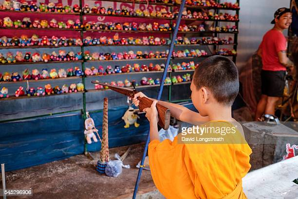 Novice Buddhist monk shoots an air rifles at a carnival location during the Ghost Festival The Phi Ta Khon festival is usually held over a three day...