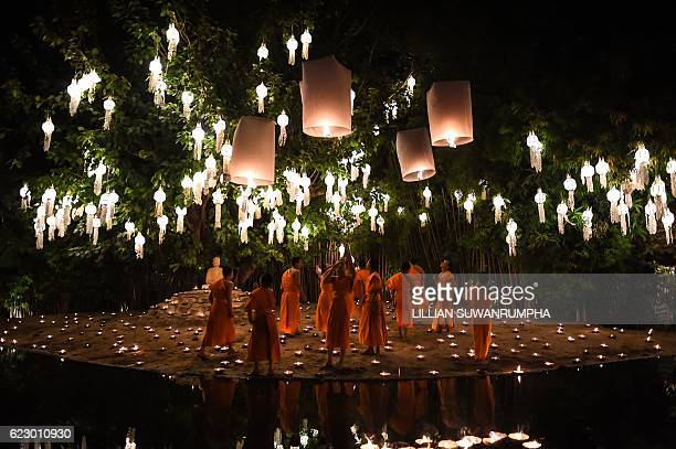 Novice Buddhist monks light lanterns for tourists to photograph at Wat Phan Tao temple to mark the beginning of the annual Yi Peng festival in the...