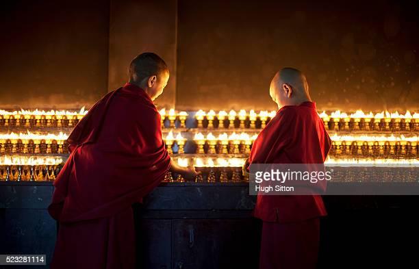 novice buddhist monks lighting candles in temple - hugh sitton fotografías e imágenes de stock