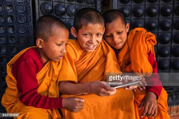 携帯電話、バクタプルで遊ぶ初心者の仏教の僧侶 - バクタプル ストックフォトと画像