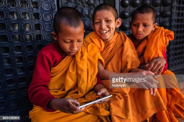 Novice Buddhist monks playing on mobile phone, Bhaktapur