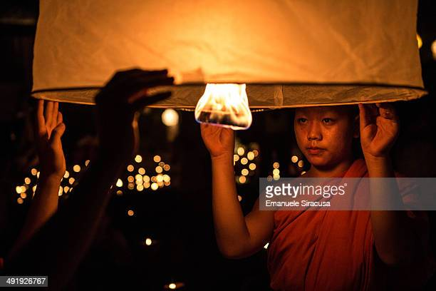 Novice Buddhist monks prepare to release a lantern as part of the Loi Krathong celebration in Wat Pahn Tao, a Buddhist temple in Chiang Mai, Thailand.