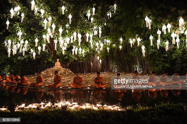 TOPSHOT Novice Buddhist monks sit to pray at Wat Phan Tao temple to mark the beginning of the annual Yi Peng festival in the popular tourist city of...