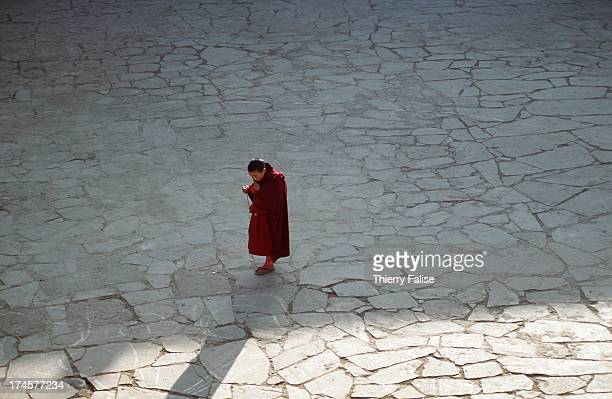 A novice crossing the main square at the Tawang monastery