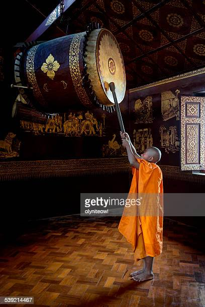 Novice Monk Beating The Drum In The Temple Hall