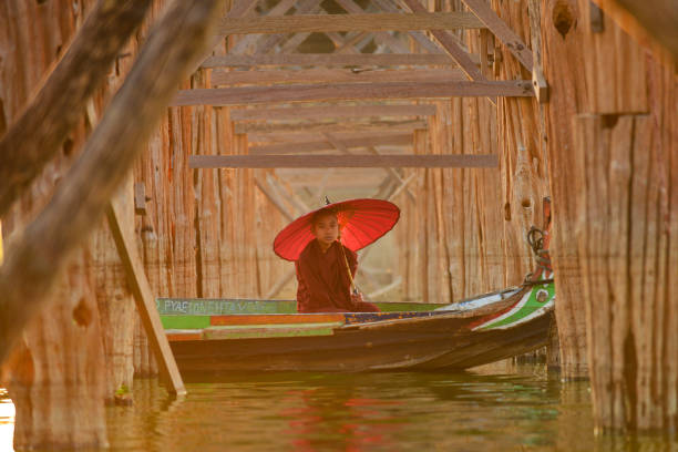 Novice monk in a boat under U Bein bridge at sunrise, Mandalay, Myanmar