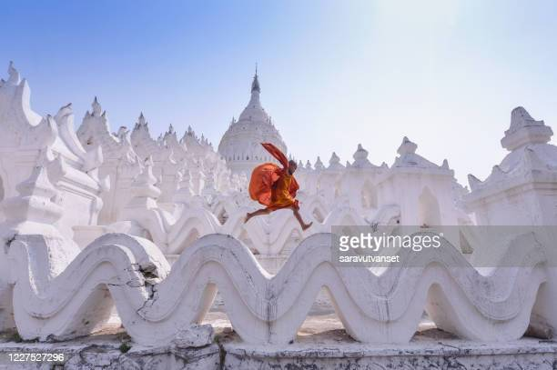 novice monk jumping on traditional temple, myanmar - spiritual enlightenment stock pictures, royalty-free photos & images