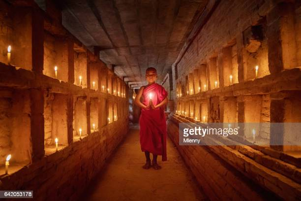 Novice Monk praying inside temple full burning candles Bagan Myanmar