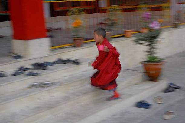 A Novice Monk Races In Late For Evening Prayers At The Druk