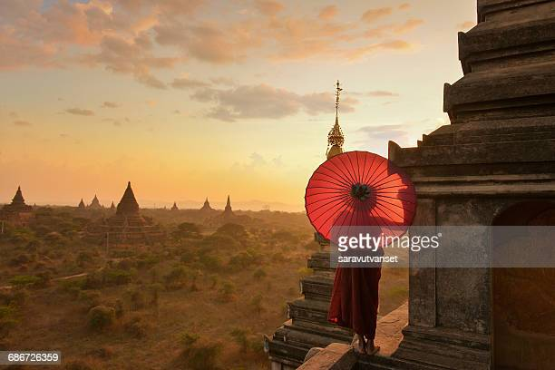 Novice Monk standing on temple at sunset, Bagan Myanmar