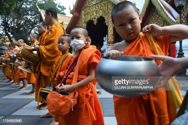 A novice monk wears a face mask in Doi Suthep Buddhist temple in the northern Thai province of Chiang Mai on April 3 2019 The city has far eclipsed...