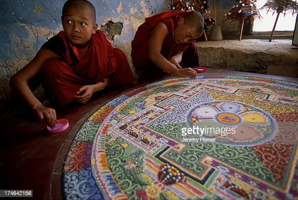 Novice monks at Semtokha Monastery prepare a mandala sand painting As the sand is dispursed the prayer is said to be answered