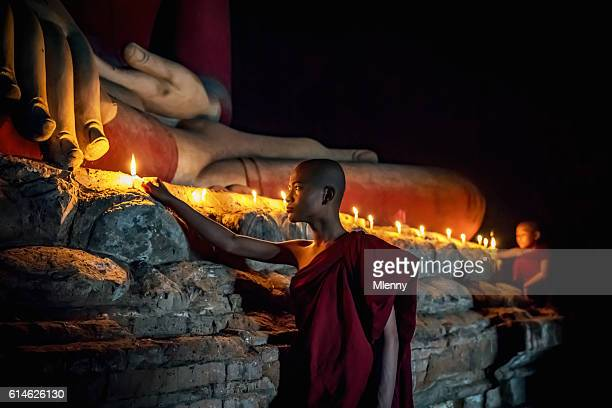 Novice Monks lighting Candles to worship Buddha Temple Bagan Myanmar