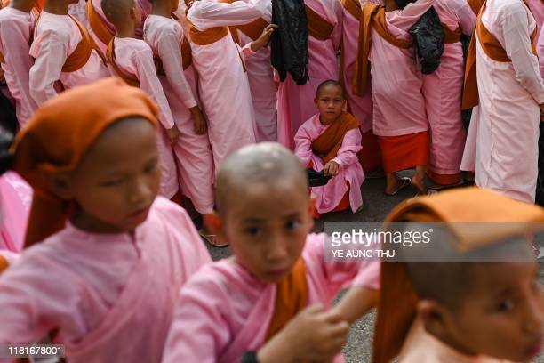 Novice nuns walking for alms procession during the Kahtain festival a Buddhist religious celebration in Yangon on November 11 2019