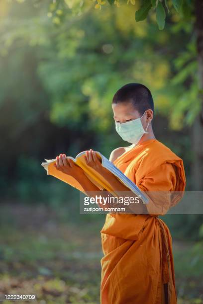 novice reading a book and wearing mask meditation under a tree in the temple with lifestyle new normal - new normal stock pictures, royalty-free photos & images