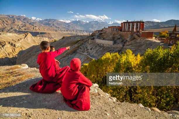 novice tibetan monks looking at the view near tsarang village, upper mustang, nepal - lo manthang stock pictures, royalty-free photos & images
