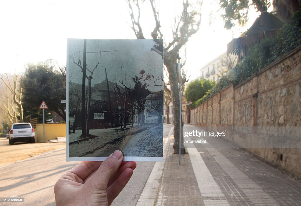 Now and then, holding picture by hand on street. : Stock Photo