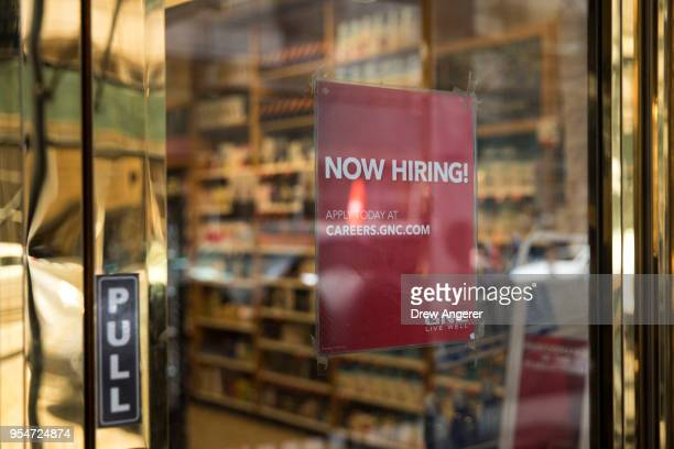A 'now hiring' sign hangs on the door of a GNC Nutrition store in Lower Manhattan May 4 2018 in New York City US unemployment fell to a near historic...