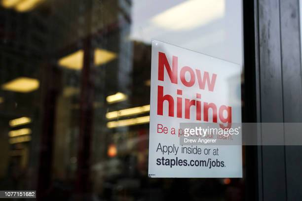 A 'now hiring' sign hangs on the door of a Staples store in Lower Manhattan January 4 2019 in New York City Following a strong December jobs report...