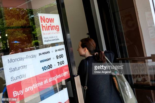 A 'now hiring' sign is displayed on the front entrance to a Staples store June 2 2017 in New York City While US unemployment has hit it lowest level...