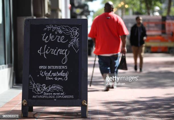A now hiring sign is posted in front of an Anthropologie store on June 1 2018 in San Francisco California The US Labor Department announced that US...