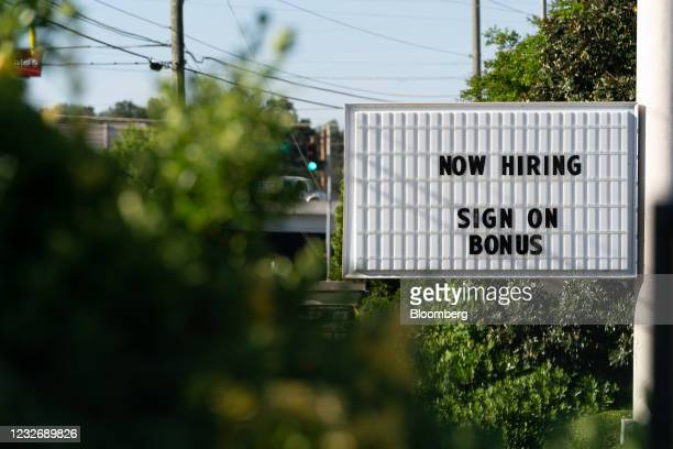 """Now Hiring"""" sign outside a business in Lithonia, Georgia, U.S., on Monday, April 26, 2021. The U.S. Economy is on a multi-speed track as minorities..."""