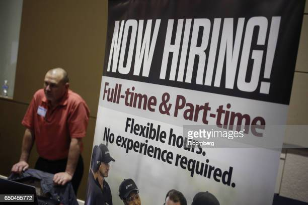 A Now Hiring sign stands on display next to the Jiffy Lube International Inc booth during a Job News USA career fair in Overland Park Kansas US on...